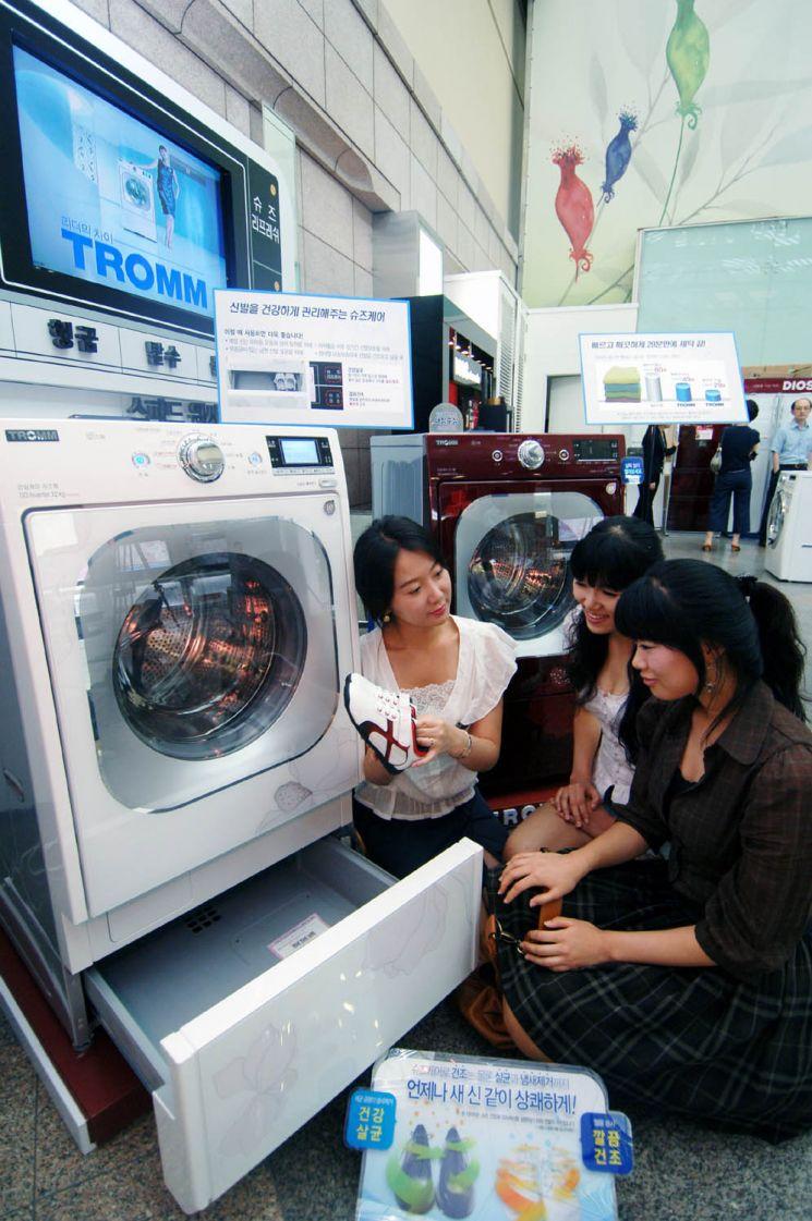 LG전자가 2008년 출시한 드럼세탁기에 탑재된 서랍형 신발관리기를 고객들이 체험하고 있다.[사진=LG전자 제공]