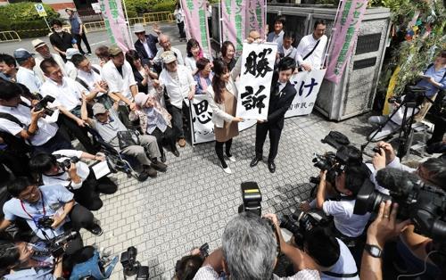 한센병 전 환자의 가족들이 2019년 6월 28일 구마모토지방법원 앞에서 '승소'라고 적힌 펼침막을 들어 보이며 기뻐하고 있다. [사진출처=연합뉴스]