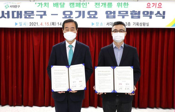 문석진 서대문구청장(왼쪽)과 박해웅 딜리버리히어로 코리아 부사장이 '가치 배달 캠페인' 전개를 위한 업무협약을 맺은 뒤 협약서를 들어 보이고 있다.
