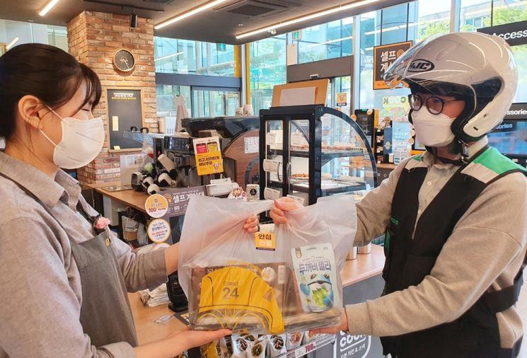 이마트24 매장에서 배달원이 다람이 봉투에 담긴 상품을 건네받고 있다(사진제공=이마트24).