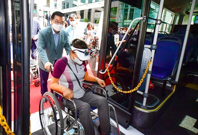 류경기 중랑구청장(왼쪽)이 지난해 중랑구 교통약자 무료셔틀버스 신차 교체 기념 시승식에서 장애인 휠체어를 밀어 장애인 승차를 돕고 있다.