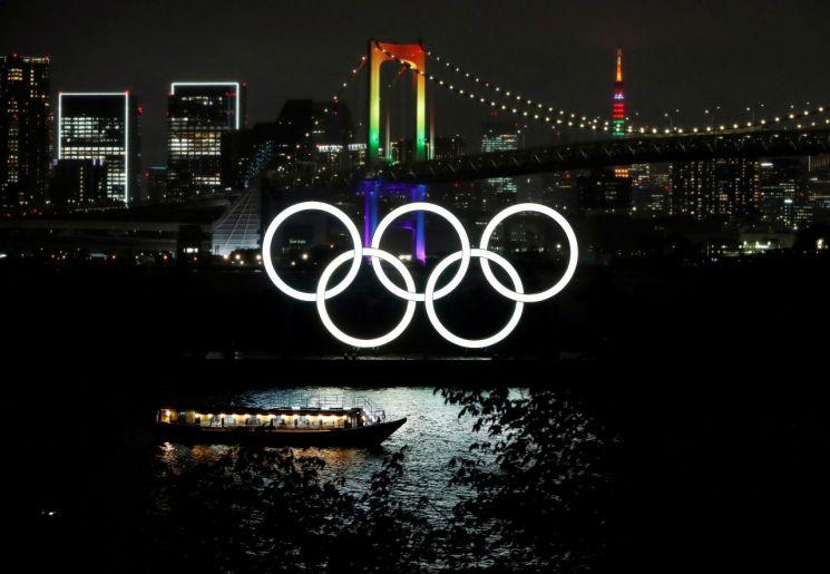 일본 도쿄의 미나토구에 있는 레인보우 브리지와 도쿄 타워에 지난 14일 '도쿄올림픽 D-100'을 축하하기 위해 올림픽 색상의 조명이 투영되고 있다. [이미지출처=연합뉴스]