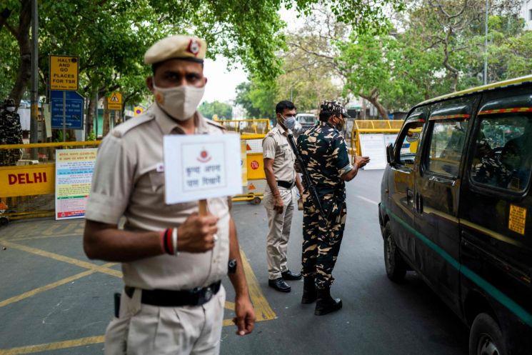 인도가 신종 코로나바이러스 감염증(코로나19) 확산으로 비상인 가운데 20일(현지시간) 수도 뉴델리에서 경찰이 도로를 막고 경계를 서고 있다. 뉴델리는 코로나19 하루 확진자가 2만5천여 명에 달하는 등 급증세를 보이자 전날 오후 10시부터 26일 오전 5시까지 일주일간 봉쇄령을 내렸다. [이미지출처=연합뉴스]