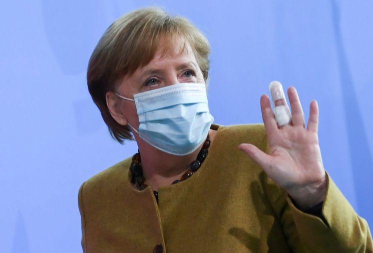 앙겔라 메르켈 독일 총리가 13일(현지시간) 베를린에서 각의를 주재한 뒤 브리핑을 마치면서 밴드를 붙인 손을 들어 보이고 있다. [이미지출처=연합뉴스]