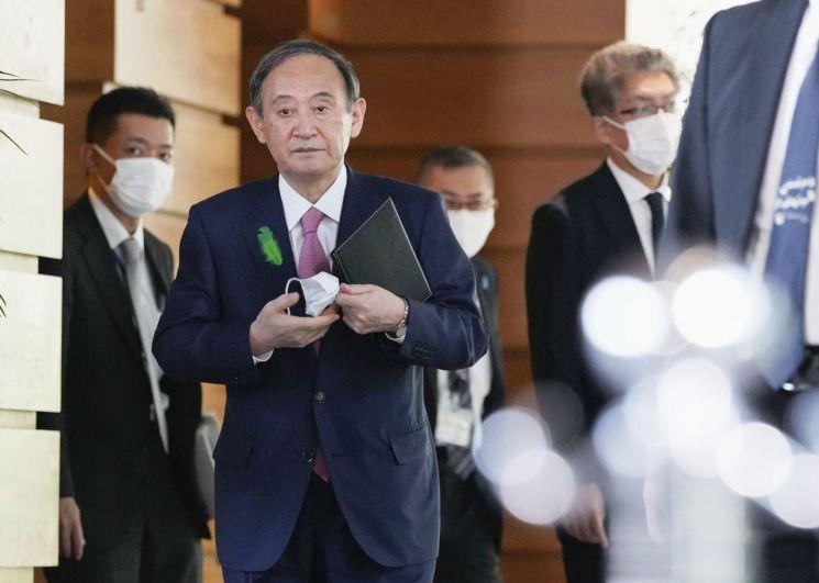 스가 요시히데(菅義偉) 일본 총리가 19일 오전 일본 총리관저에서 기자들의 취재에 응하기 위해 마스크를 벗고 이동하고 있다. [이미지출처=연합뉴스]