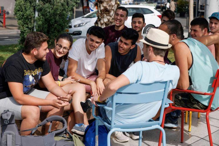 이스라엘이 실외 마스크 착용 의무를 해제한 첫날인 18일(현지시간) 텔아비브 거리에서 젊은이들이 마스크를 벗은 채 다닥다닥 붙어 앉아 이야기를 나누고 있다. [이미지출처=연합뉴스]