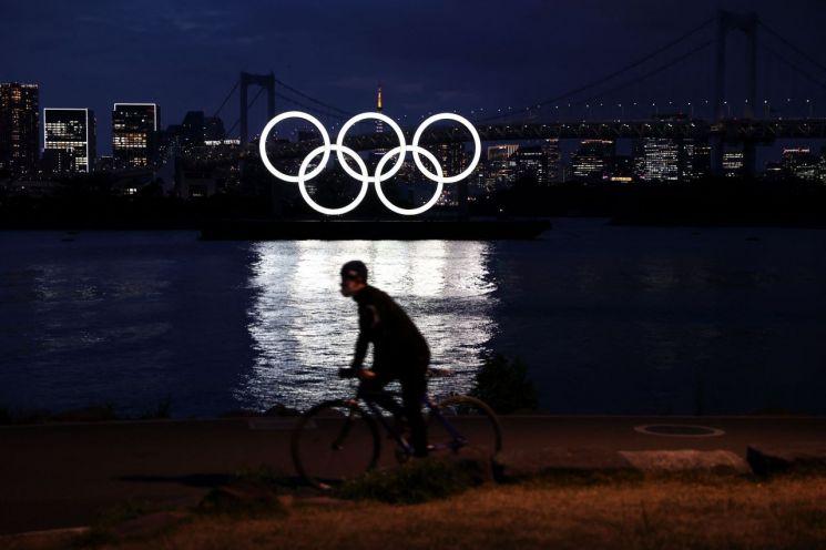 일본 도쿄의 오다이바 해양공원에 설치된 오륜 조형물 앞에서 지난 12일 한 남성이 자전거를 타고 있다. [이미지출처=연합뉴스]