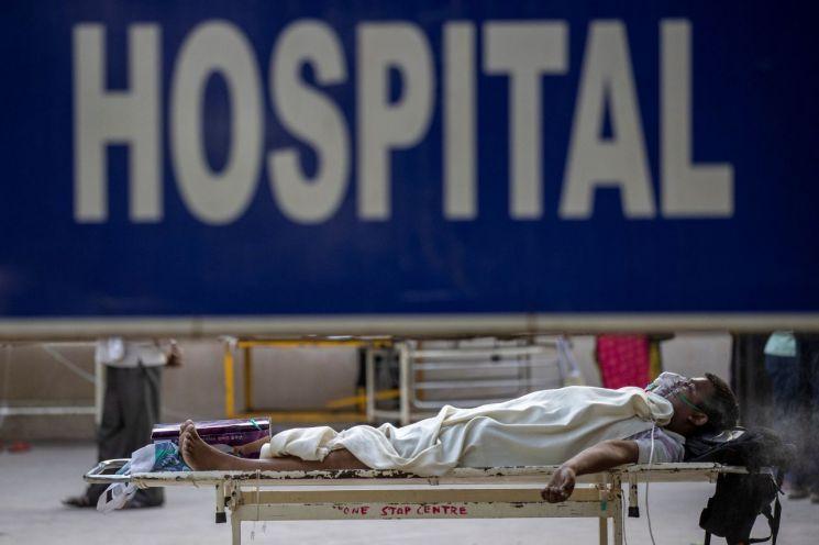 인도가 코로나19 확산으로 비상인 가운데 23일(현지시간) 수도 뉴델리의 그루 테그 바하두르 병원 밖에서 한 코로나19 환자가 입원을 기다리며 임시 병상에 누워 있다. [이미지출처=로이터연합뉴스]