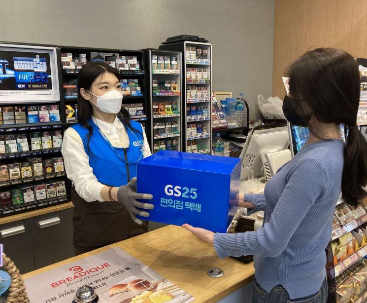고객이 GS25에서 점원에게 접수한 반값택배를 건네고 있다.