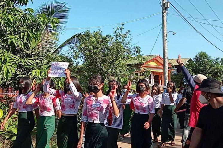 미얀마 군부 쿠데타 규탄 시위대가 빨간 색칠을 한 옷을 입고 독재에 대한 저항의 상징인 '세 손가락 경례'를 하고 있다. [이미지출처=연합뉴스]