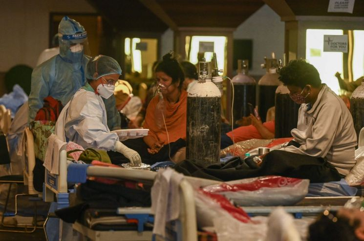 인도 수도 뉴델리의 신종 코로나바이러스 감염증(코로나19) 임시 병동에서 7일(현지시간) 개인보호장비를 착용한 의료진이 코로나19 환자들을 돌보고 있다. [이미지출처=연합뉴스]