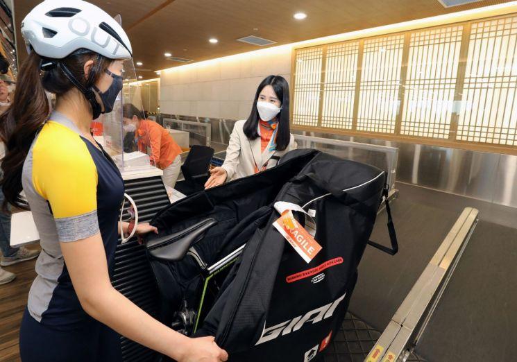 제주항공 직원이 자전거를 가지고 제주도 여행을 떠나는 승객에게 '자전거 캐링백 서비스'를 소개하고 있다. 해당 서비스는 항공운송용 자전거 캐링백을 제공해 목적지까지 자전거를 안전하게 운송해준다.