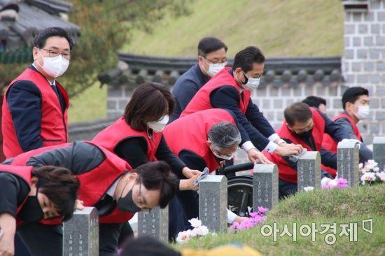 국민의힘 초선의원들이 10일 광주광역시 국립5.18민주묘지 참배 이후 묘비를 닦고 있다.