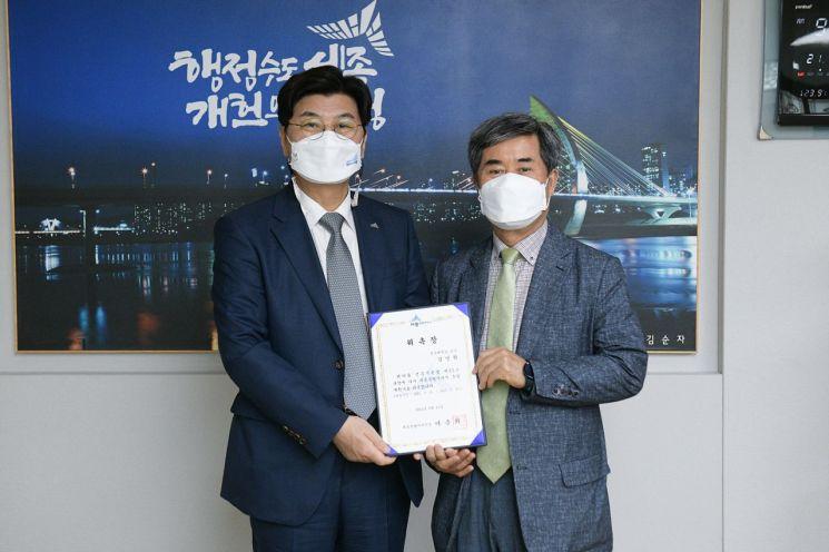 이춘희 세종시장(왼쪽)이 11일 김영환 교수(오른쪽)에게 총괄계획가 위촉장을 전달한 후 기념촬영을 하고 있다. 세종시 제공