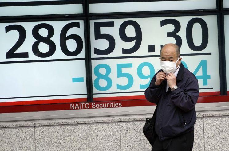 11일 일본 도쿄의 한 길거리에서 닛케이지수가 하락하고 있는 것을 보여주는 전광판 앞으로 시민 한 명이 걸어가고 있다. [이미지출처=EPA연합뉴스]