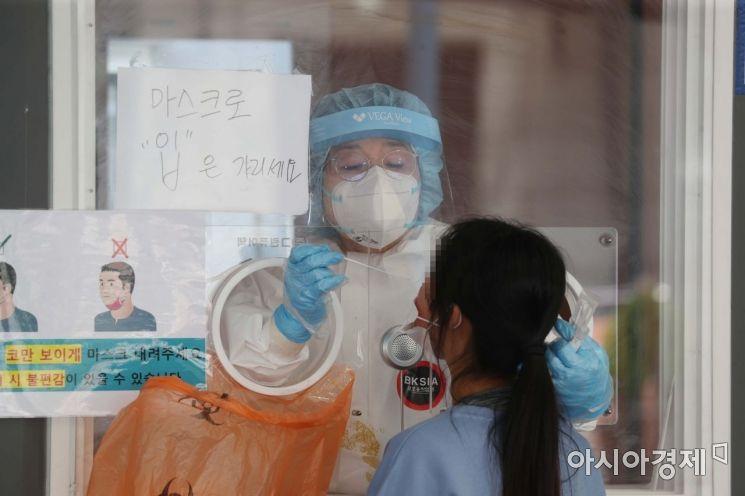 국제 간호사의 날인 12일 서울역 광장에 마련된 코로나19 임시 선별검사소에서 의료진이 검체 채취를 하고 있다. /문호남 기자 munonam@