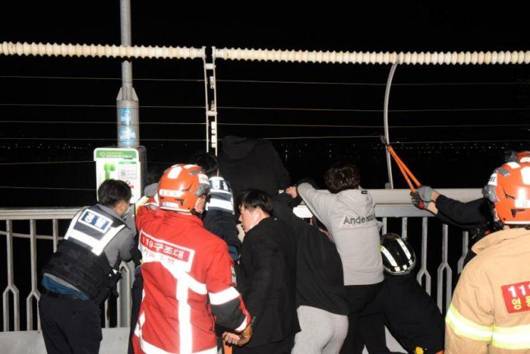 서울 환일고 고등학생 4명이 5월 1일 오전 서울 마포대교 북단 방향 근처에서 20대 남성이 투신하려는 것을 막고 경찰관과 구조를 하고 있다.