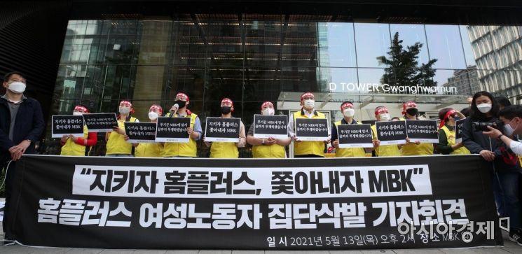 홈플러스 노동자들이 지난 13일 서울 광화문 디타워 앞에서 MBK파트너스의 주요 점포 폐점·매각을 규탄하며 집단 삭발 시위를 벌이고 있다.