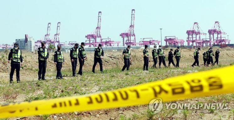 40대 손님을 살해하고 시신을 유기한 혐의로 주점 업주를 체포한 지난 12일 인천시 연수구 한 공터에서 경찰들이 피해자의 시신을 찾기 위해 수색하고 있다. [이미지출처=연합뉴스]