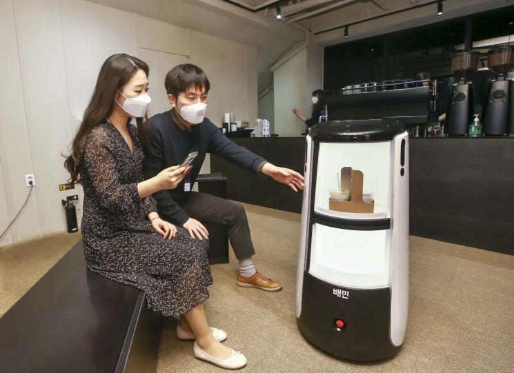 D타워 광화문에서 배달로봇 딜리타워를 이용해 커피 배달 서비스를 시연하고 있다.