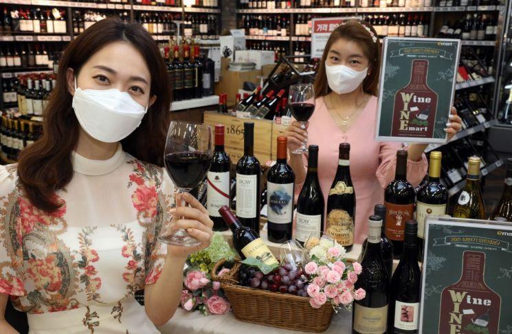 지난 12일 오전 이마트 용산점 와인 매장에서 모델들이 '상반기 와인장터' 행사를 소개하고 있다.