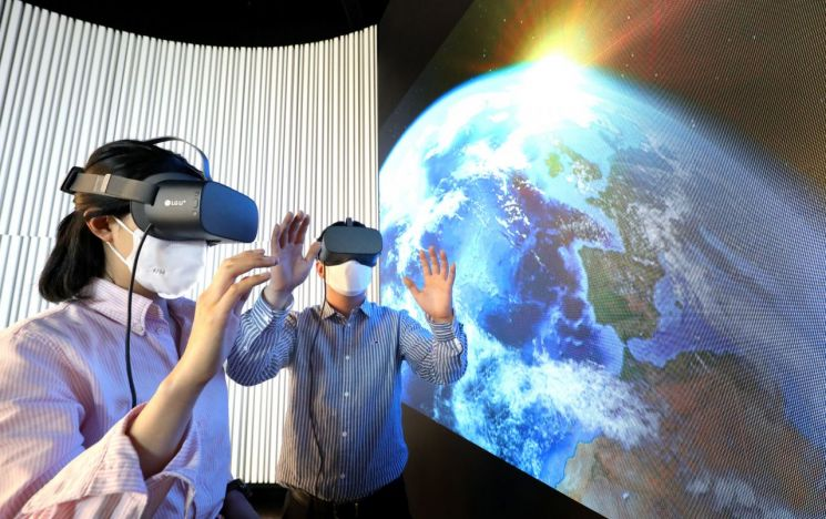 LG유플러스 관계자들이 우주를 배경으로 한 스튜디오에서 U+VR의 신규 콘텐츠를 감상하는 모습.