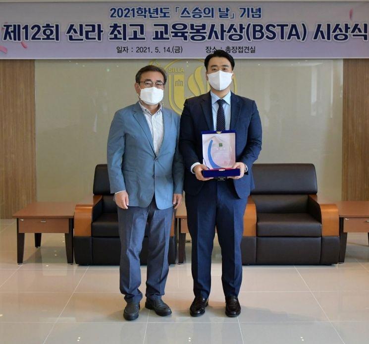 신라대 최고 교육봉사상을 수상한 이상훈 교수(오른쪽)가 김충석 총장과 기념촬영하고 있다.