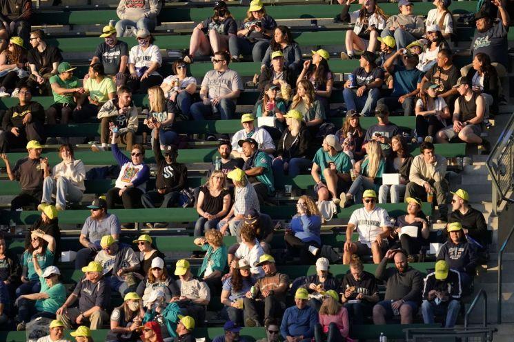 미국 워싱턴주 시애틀에 있는 '시애틀 매리너스' 홈구장에서 14일(현지시간) 신종 코로나바이러스 감염증(코로나19) 예방 마스크를 쓰지 않은 관중이 매리너스가 '클리블랜드 인디언스'를 맞아 벌이는 야구 경기를 즐기고 있다. 구단 측은 코로나19 백신 접종 완료자를 위해 마스크 착용과 사회적 거리두기를 지키지 않아도 되는 특별구역을 관중석에 마련했다. [이미지출처=연합뉴스]