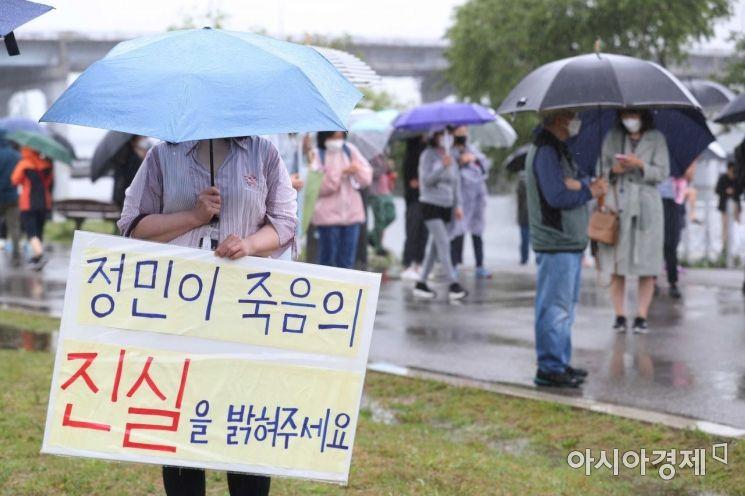 지난 16일 서울 반포한강공원 수상택시 승강장 인근에서 열린 '고 손정민 군을 위한 평화집회'에서 참가자들이 우산을 쓴 채 사건의 진상규명을 촉구하고 있다.