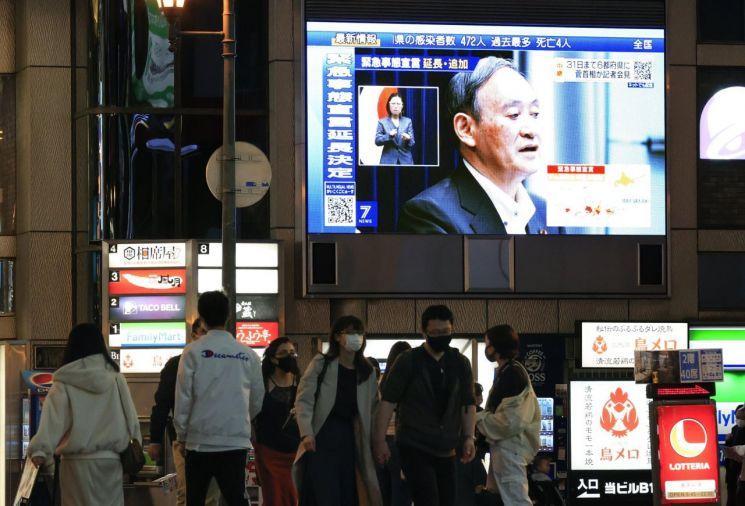 지난 7일 오후 스가 요시히데 일본 총리가 코로나19 긴급사태에 관한 기자회견을 하는 모습이 일본 오사카시 도심에 설치된 대형 스크린에 중계되고 있다. [이미지출처=연합뉴스]