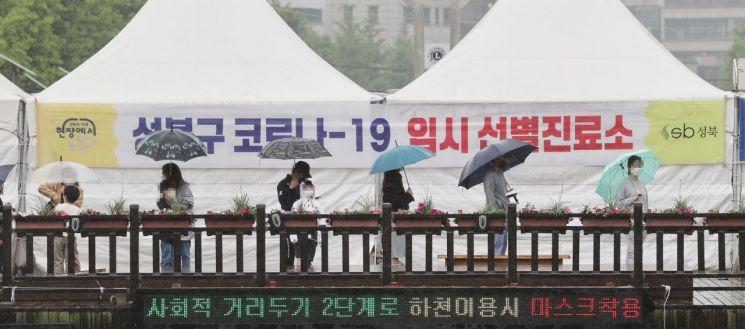 16일 오전 서울 성북구청 앞에 설치된 임시선별진료소에서 시민들이 우산을 쓰고 검사를 위해 대기해 있다. [이미지출처=연합뉴스]