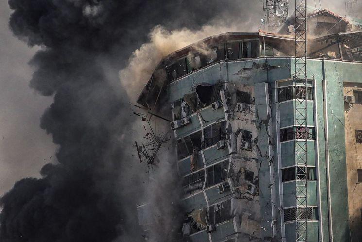 15일(현지시간) 외신들이 다수 입주한 팔레스타인 가자지구 내 '잘라 타워'가 이스라엘의 공습을 받고 연기를 내뿜으며 무너져 내리고 있다. [이미지출처=연합뉴스]