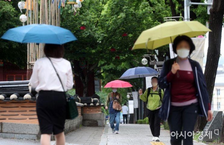 전국이 흐리고 비가 내린 17일 서울 시내의 한 거리에서 시민들이 우산을 쓴 채 발걸음을 재촉하고 있다./김현민 기자 kimhyun81@