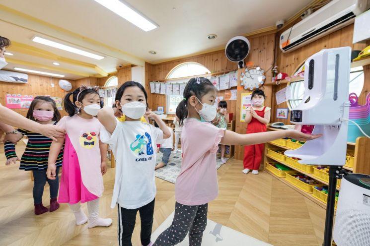 광진구 내 한 어린이집에서 아동들이 손소독 발열체크기를 사용하고 있는 모습