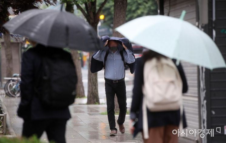 중부지방 곳곳에 비가 내린 1일 서울 광화문 인근 거리에서 우산을 준비하지 못한 한 출근길 시민이 겉옷을 덮어쓰고 발걸음을 재촉하고 있다./김현민 기자 kimhyun81@