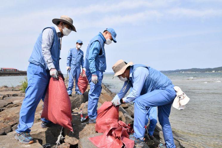 포스코케미칼 민경준 사장(가운데)을 비롯한 임직원들이 포항 청림동 해변에서 폐기물 수거 봉사활동을 하고 있다.