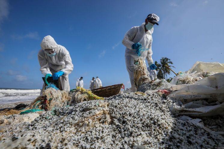스리랑카 해안에서 해군 병력이 해안으로 밀려온 플라스틱 조각들을 청소하는 작업을 진행하고 있다. [이미지출처=EPA연합뉴스]