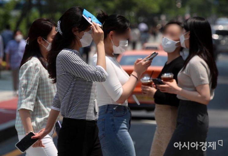 서울 한낮 최고기온이 32도까지 오르는 등 전국적으로 맑고 무더운 날씨를 보인 9일 서울 청계천 인근 거리에서 한 시민이 얼굴에 내리쬐는 햇빛을 가리며 걷고 있다./김현민 기자 kimhyun81@
