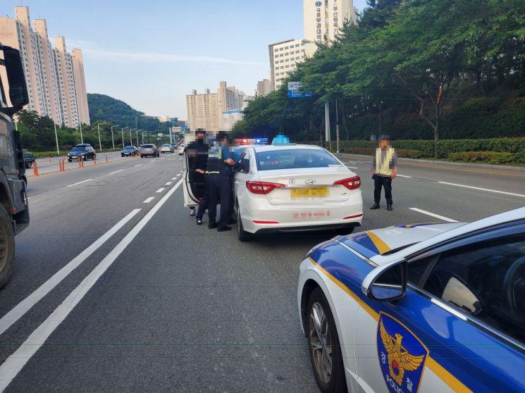 경찰이 9일 오전 6시 42분께 순찰차로 택시 앞 뒤를 막고 공군 병사 A씨를 검거하고 있다. [이미지출처=부산경찰청]