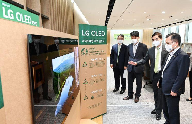 박형세 LG전자 HE사업본부장(오른쪽 두 번째)이 홍정기 환경부 차관에게 플라스틱 사용의 원천 감축이 가능한 LG 올레드 TV를 설명하고 있다.[사진제공=LG전자]