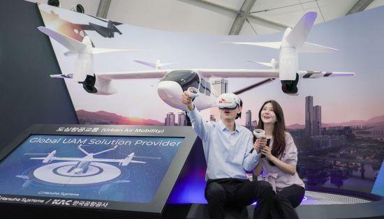SK텔레콤은 한국공항공사, 한화시스템, 한국교통연구원, 티맵모빌리티와 함께 '2021 서울스마트모빌리티엑스포'에 참여해 가상현실(VR) 기반의 도심항공교통(UAM) 탑승 체험을 선보인다고 9일 밝혔다. 사진은 SK텔레콤 모델이 VR 로 구현된 UAM 콘텐츠를 통해 상암동에서 코엑스까지 이동하는 가상 체험을 하는 모습