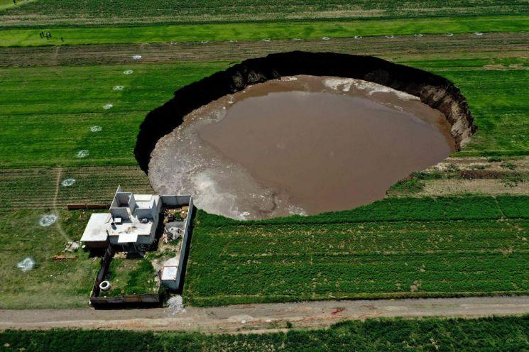 지난 1일(현지시간) 멕시코 중부 푸에블라주 산타마리아 자카테펙의 들판에 거대한 싱크홀의 모습이 보인다. [이미지출처=AFP 연합뉴스]