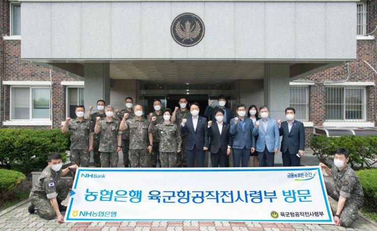 권준학 NH농협은행 은행장(사진 오른쪽에서 다섯 번째)과 임직원들이 경기도 이천에 위치한 육군항공작전사령부를 방문하여 기념촬영을 하고 있다.