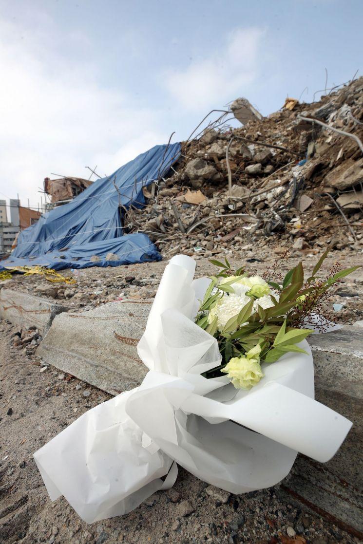 13일 오전 광주 동구 학동4 재개발 구역 철거 건물 붕괴 사고 현장 건너편 도로에 피해자를 추모하는 꽃다발과 손편지가 놓여있다. 지난 9일 오후 4시 22분께 이곳에서 철거 중이던 5층 건물이 붕괴하며 잠시 정차 중이던 시내버스를 덮쳤다. 이 버스에 타고 있던 17명 가운데 9명은 숨지고 8명은 중상을 입었다. [이미지출처=연합뉴스]