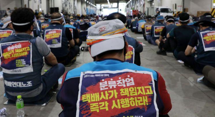 지난 9일 서울복합물류센터에서 한 우체국 택배기사가 파업 결의대회에 참석하고 있다. 택배노조는 2차 사회적 합의 결렬로 이날부터 무기한 전면파업에 돌입했다. [이미지출처=연합뉴스]