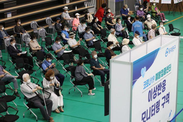 서울 동대문구체육관에 마련된 예방접종센터에서 시민들이 접종 후 이상반응 모니터링을 위해 앉아있다. [이미지출처=연합뉴스]