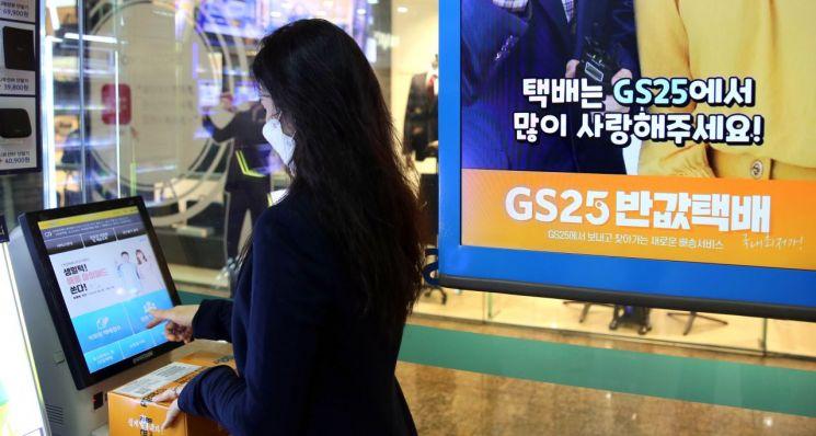 한 고객이 GS25 편의점 내 키오스크에서 반값택배를 접수하고 있다.