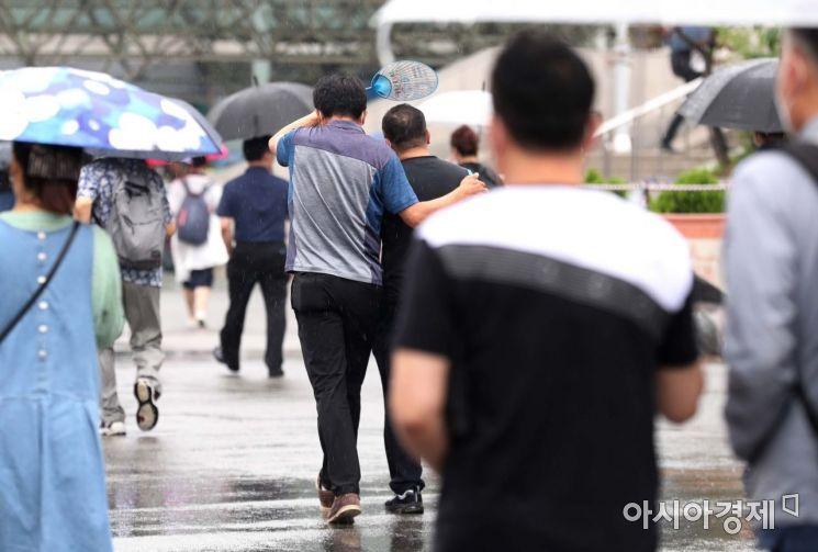 [포토]부채로 비 피하는 시민들
