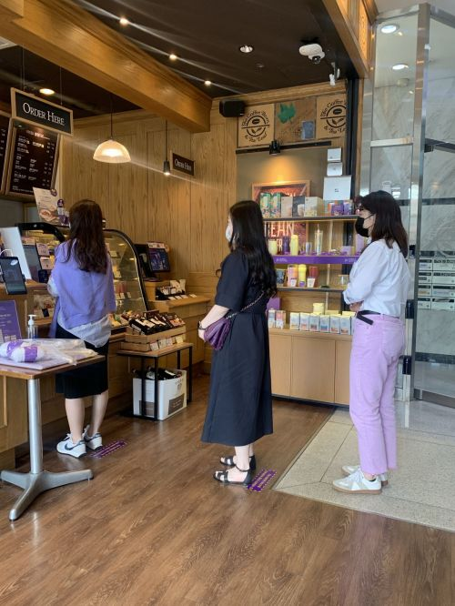 커피빈코리아 임직원들이 16일 서울시 강남구 본사 내 매장에서 보라색 패션아이템을 착용한 채 음료를 주문하고 있다. 사진=커피빈코리아 제공