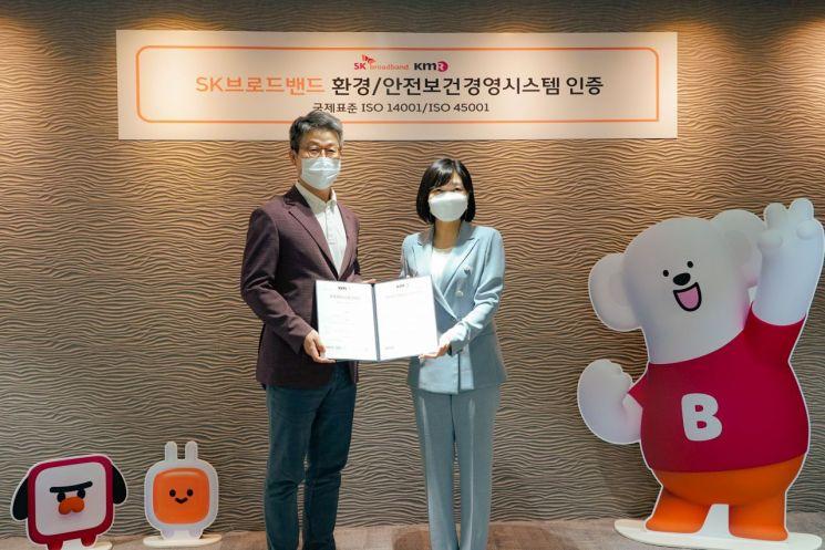 최진환 SK브로드밴드 사장(왼쪽)이 황은주 한국경영인증원 원장으로부터 ISO14001(환경경영시스템)과 ISO45001(안전보건경영시스템) 인증서를 받고 있다.